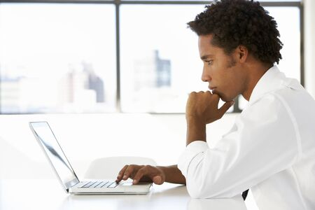 working desk: Businessman Sitting At Desk In Office Using Laptop