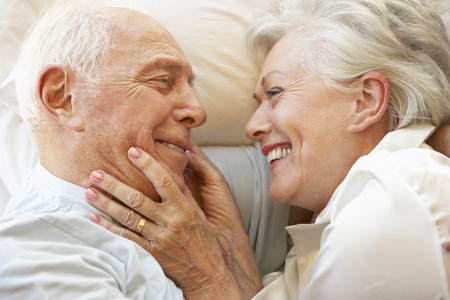 Senior paar ontspannen in bed Stockfoto