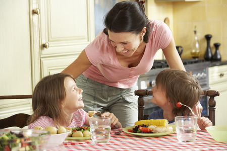 母はキッチンで子どもたちに食事を提供