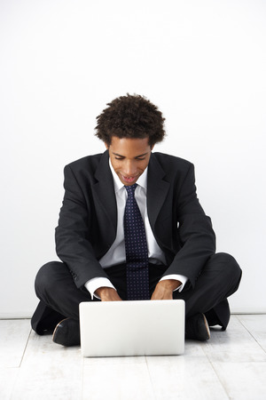 Studio Portrait Of Businessman Sitting On Floor Using Laptop Stok Fotoğraf