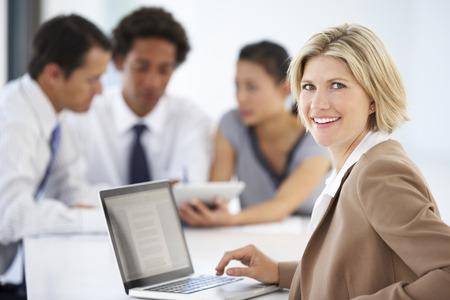 Retrato de la hembra Ejecutivo Usar el portátil con una Reunión de oficinas en el fondo Foto de archivo - 42251824