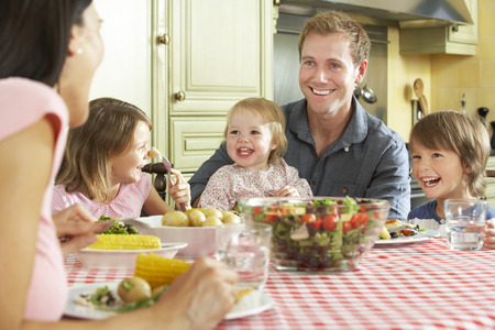 sitting at table: Family Eating Meal Together In Kitchen