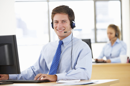 Friendly Service Agent Talking To Customer In Call Centre Stock Photo