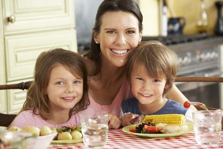 Madre que sirve comidas a los niños en la cocina