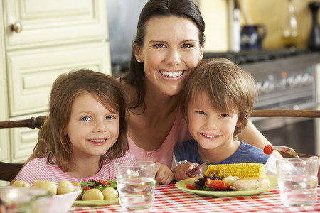eating food: Mother Serving Meal To Children In Kitchen