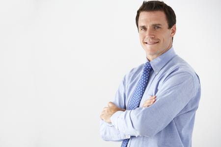 ejecutivo en oficina: Retrato del estudio del hombre de negocios de pie contra el fondo blanco