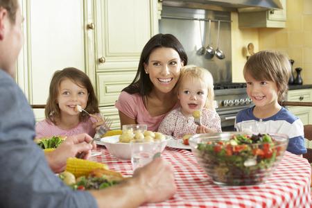 família: Família que come a refeição junto na cozinha Banco de Imagens