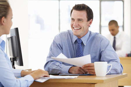 discussing: Businesswoman And Businessman Working At Desk Together Stock Photo