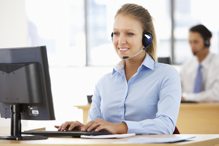 Friendly Service Agent Talking To Customer In Call Centre 스톡 콘텐츠