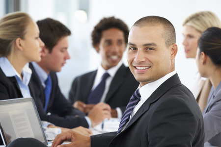 hispanic people: Portrait Of Male Executive With Office Meeting In Background Stock Photo