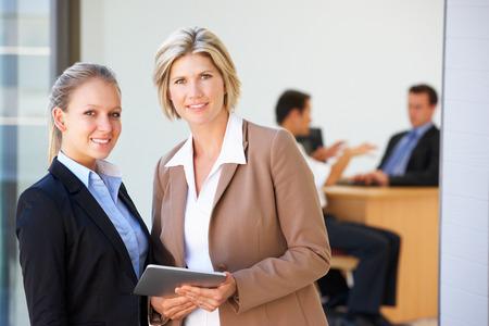 mixed age range: Dos Mujeres Ejecutivas Uso de Tablet PC Con Reuni�n Oficina En El Fondo Foto de archivo