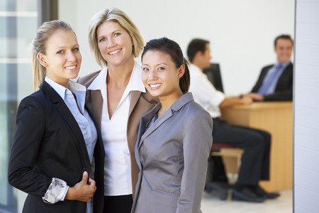 mixed age range: Portrait Of Three Female Executives With Office Meeting In Background