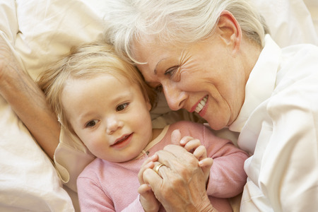 Grandmother Cuddling Granddaughter In Bed