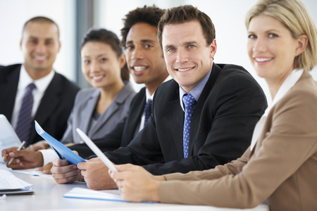 happy workers: Portrait Of Male Executive Attending Office Meeting With Colleagues Stock Photo