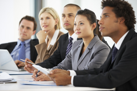 business relationship: Group Of Business People Listening To Colleague Addressing Office Meeting