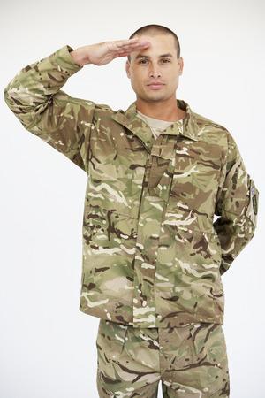 Retrato del estudio del soldado con uniforme y saludando Foto de archivo