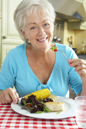 eating dinner: Senior Woman Eating Meal In Kitchen Stock Photo