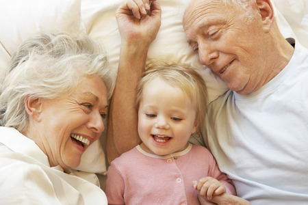 grandpa and grandma: Grandparents Cuddling Granddaughter In Bed
