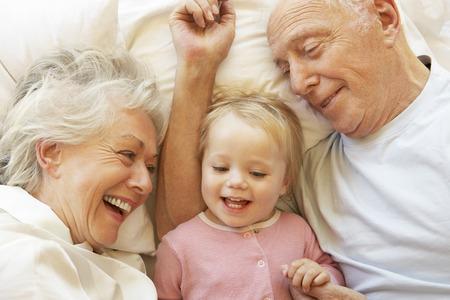 cuddling: Grandparents Cuddling Granddaughter In Bed