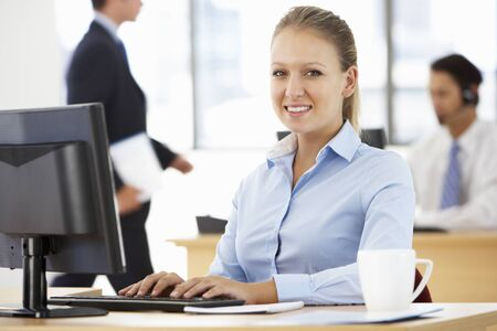office desk: Businesswoman Working At Desk In Busy Office Stock Photo