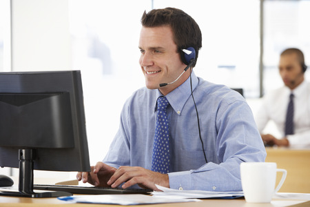 Friendly Service Agent Talking To Customer In Call Centre Standard-Bild
