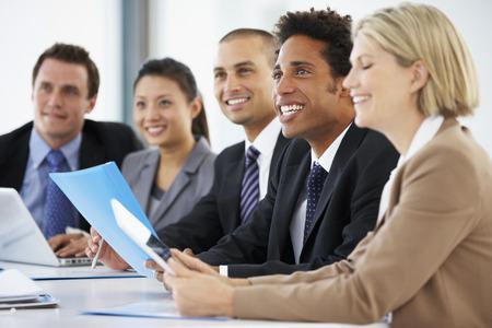negócio: Grupo de executivos que escuta o colega Dirigindo reunião do escritório