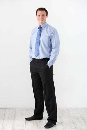 standing against: Studio Portrait Of Businessman Standing Against White Background Stock Photo