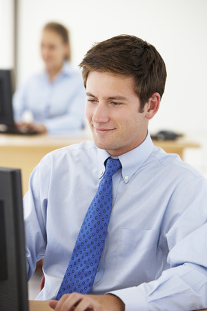 young office workers: Businessman Working At Desk In Busy Office Stock Photo