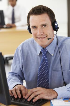 telephonist: Friendly Service Agent Talking To Customer In Call Centre Stock Photo