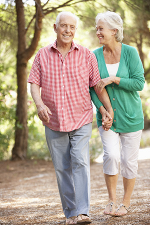 person walking: Senior Couple Walking In Countryside Together