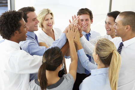 business relationship: Close Up Of Business People Joining Hands In Team Building Exercise Stock Photo