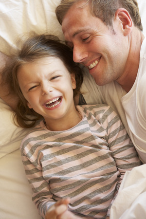 tickling: Father And Daughter Relaxing In Bed
