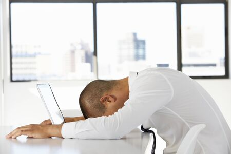 ラップトップを使用してオフィスで机に座っている不満の実業家