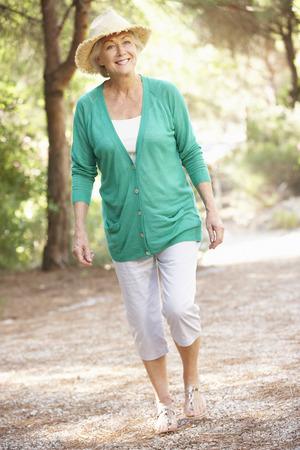 chapeau de paille: Femme senior Walking In Campagne Banque d'images