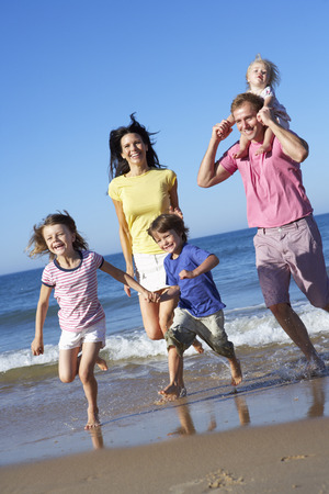 4 5 year old: Family Running Along Beach Together