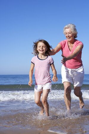 grandmother grandchild: Grandmother Chasing Granddaughter Along Beach