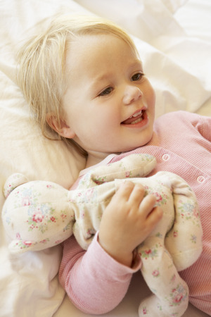 old girl: Young Girl Relaxing In Bed With Toy Stock Photo