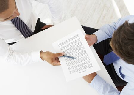 Overhead View Of Two Businessmen Working At Desk Together Stock Photo