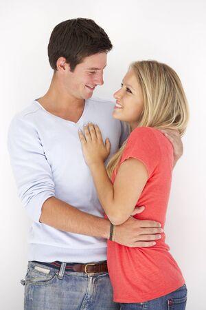 pareja abrazada: Retrato del estudio romántico Abrazar Pareja joven contra el fondo blanco