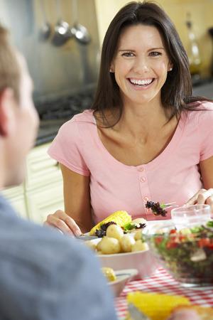 dieta sana: Pares que comen la comida junto en cocina