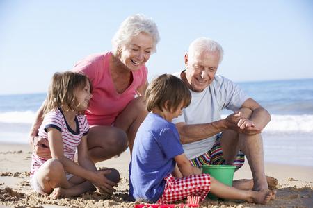 祖父母と孫建物ビーチの砂の城 写真素材