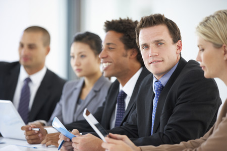 mixed age range: Portrait Of Male Executive Attending Office Meeting With Colleagues Stock Photo
