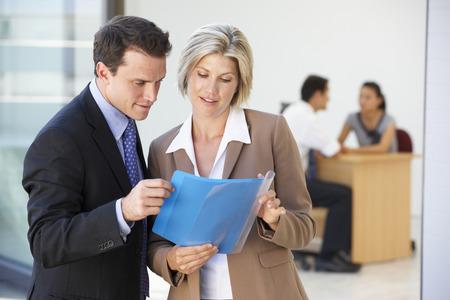 čtyři lidé: Samci a samice výkonný projednávání zprávy s Office setkání v pozadí