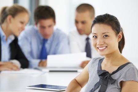 ejecutivo en oficina: Retrato De Mujer Ejecutiva Con Office reunión de fondo Foto de archivo