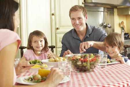 Familia que come la comida junto en cocina