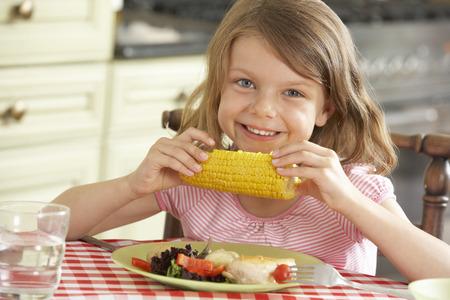 mazorca de maiz: Chica joven que come la comida en cocina