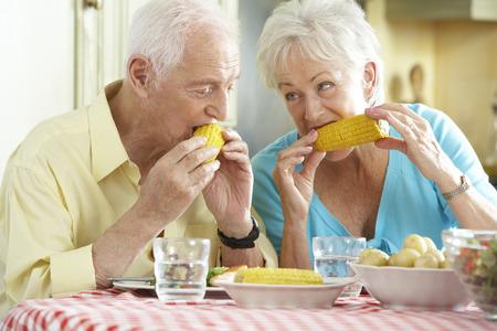 mazorca de maiz: Pareja mayor que come comida junto en cocina
