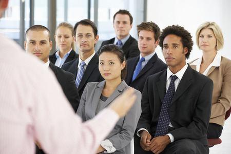 office worker: Group Of Business People Listening To Speaker Giving Presentation