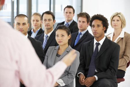 empleado de oficina: Grupo de hombres de negocios que escucha el altavoz Presentaci�n Dar