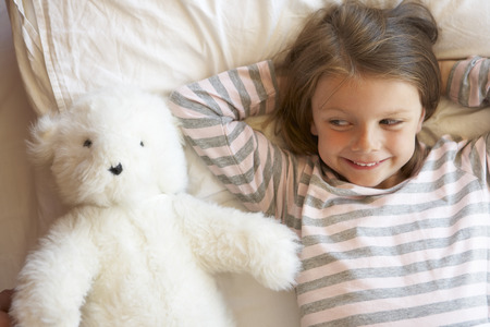 cuddly toy: Young Girl Relaxing In Bed With Toy Stock Photo